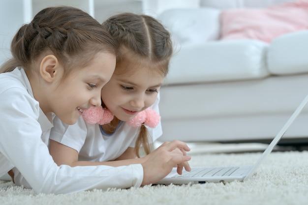 Śliczne małe dziewczynki patrzące na laptopa w domu