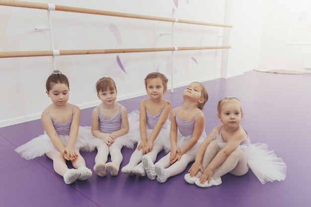 Śliczne małe dziewczynki siedzi na podłodze, odpoczywa po lekcji baletu w studio tańca