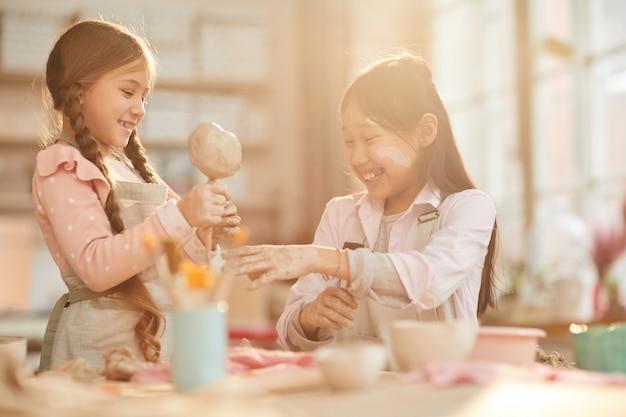 Śliczne małe dziewczynki w studiu garncarskim