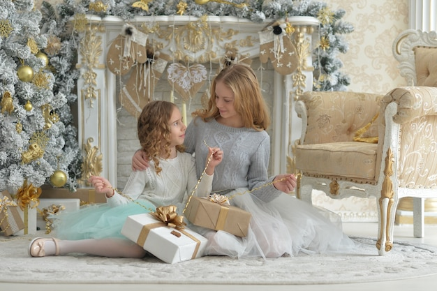 Śliczne małe dziewczynki z prezentami w pobliżu udekorowanej choinki