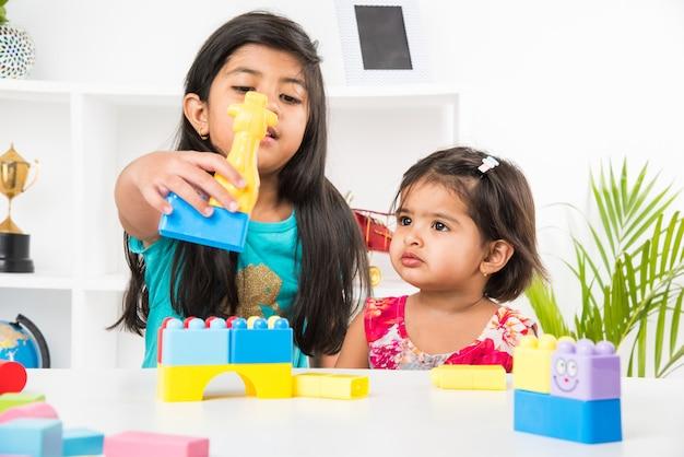 Śliczne małe indyjskie azjatki bawią się zabawkami lub klockami i bawią się siedząc przy stole