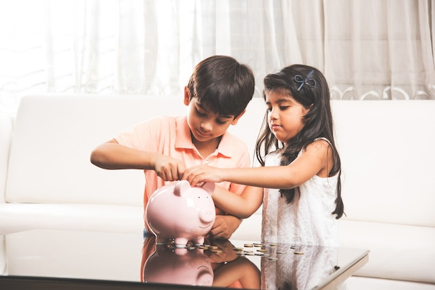 Śliczne małe indyjskie azjatyckie dzieci oszczędzające monety w skarbonce w domu
