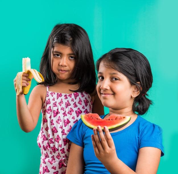 Śliczne małe indyjskie dziewczynki jedzą plasterek arbuza i banana, stojąc na białym tle nad zielonym tłem