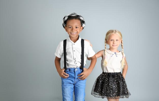 Śliczne modne dzieci na szarej powierzchni