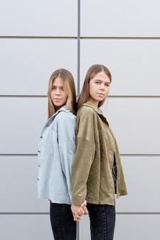Śliczne nastoletnie bliźniaczki stojące przy ścianie budynku