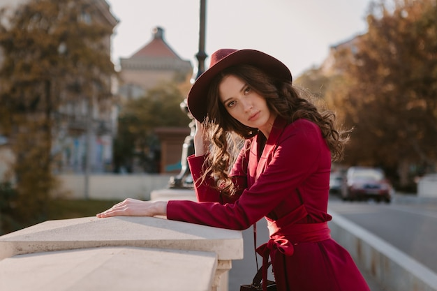 Śliczne piękne stylowe kobiety w fioletowym garniturze spaceru ulicą miasta, trend w modzie wiosna lato jesień sezon w kapeluszu, trzymając torebkę