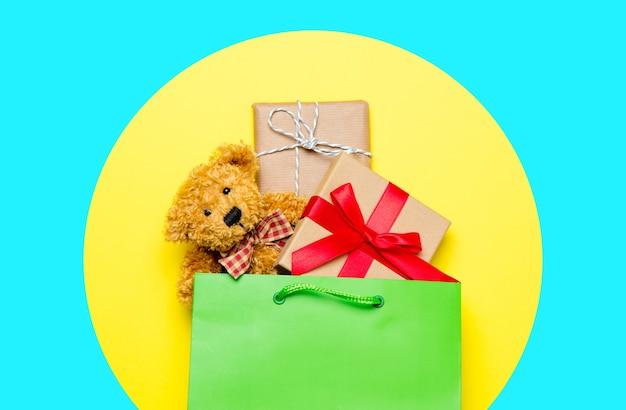 Śliczne prezenty w pięknej zielonej torbie na zakupy i misiu na cudownym żółtym tle