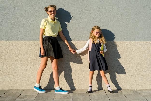Śliczne siostry uczennica w mundurek szkolny.