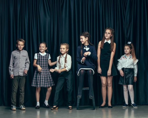 Śliczne stylowe dzieci na ciemnym tle studio. piękne nastolatki i chłopak stojący razem