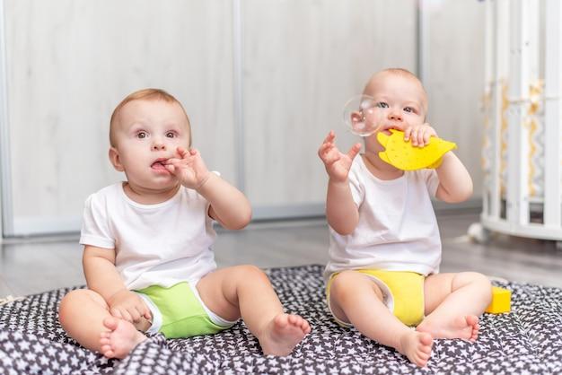 Śliczne szczęśliwe dzieci bawią się razem na podłodze zabawkami i biorą je do buzi