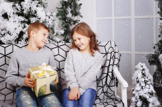 Śliczne szczęśliwe dzieci, chłopiec i dziewczynka ostatnie świąteczne pudełka na prezenty. brat i siostra dają prezenty świąteczne