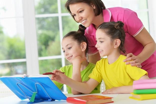 Śliczne tweenie dziewczyny i matka odrabiają pracę domową w domu