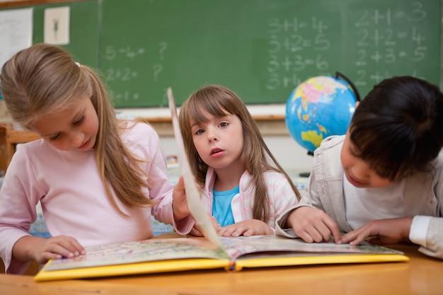 Śliczne uczennice czytając bajkę ich kolega z klasy