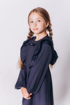 Śliczne urocze blondie kaukaski dziewczyna w mundurku szkolnym na białym tle
