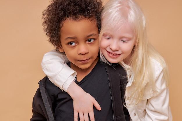Śliczne urocze zróżnicowane dzieci uśmiechnięte razem na białym tle