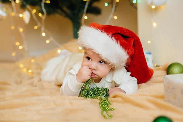 Śliczne uśmiechnięte dziecko leży pod świąteczną choinką i bawi się prezentami