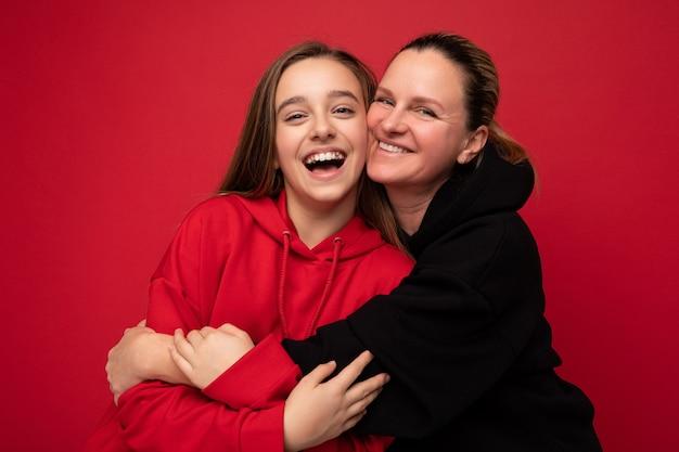 Śliczne zdjęcie strzał piękna szczęśliwa uśmiechnięta córka brunetka na sobie stylową czerwoną bluzę z kapturem i dorosłych