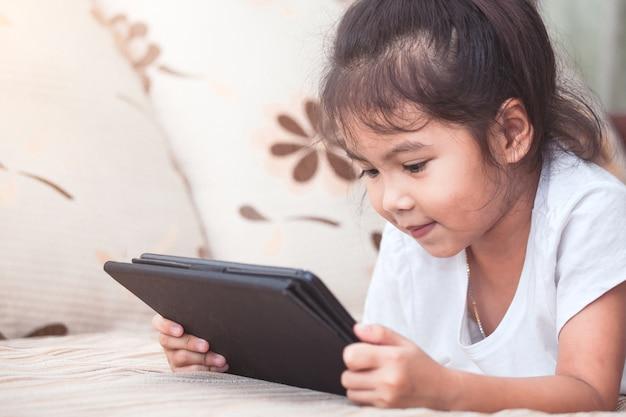 Ślicznej azjatykciej dziecko dziewczyny łgarski puszek i używać mądrze telefon, pastylka w pokoju