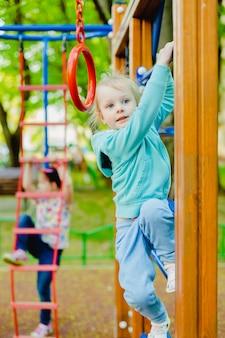 Ślicznej małej blondynki caucasian dziewczyna ma zabawę na boisku outdoors w lecie.