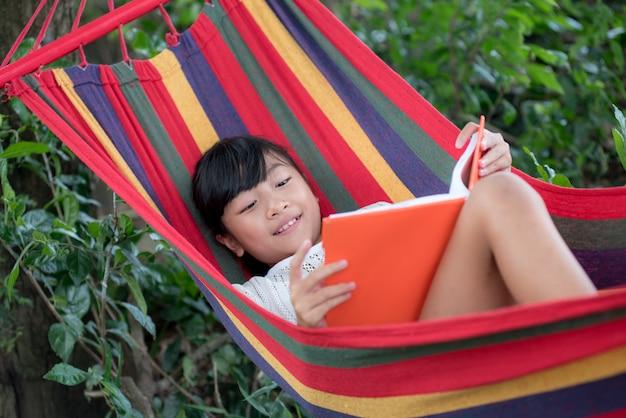 Ślicznej małej dziewczynki czytelnicza książka podczas gdy relaksujący w hamaku outdoors
