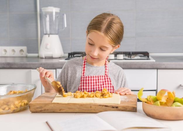 Ślicznej małej dziewczynki kładzenia jabłczany plombowanie na cieście