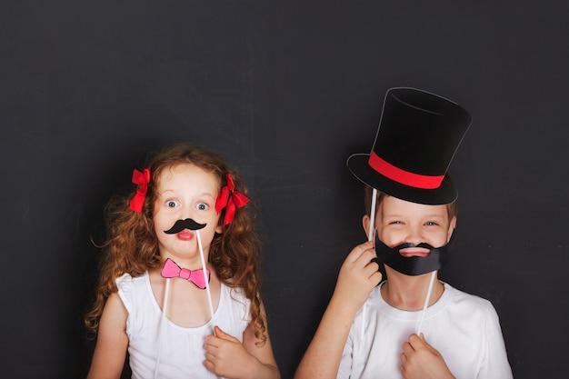 Śliczni bliźniacy dzieciaki trzymają karnawałowego wąsy i brodę