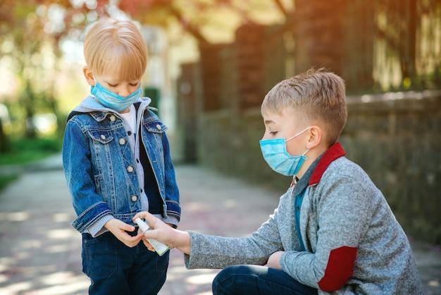 Śliczni bracia jest ubranym maski na twarz outdoors. dzieci dezynfekujące ręce żelem antyseptycznym. koronawirus wybuch.