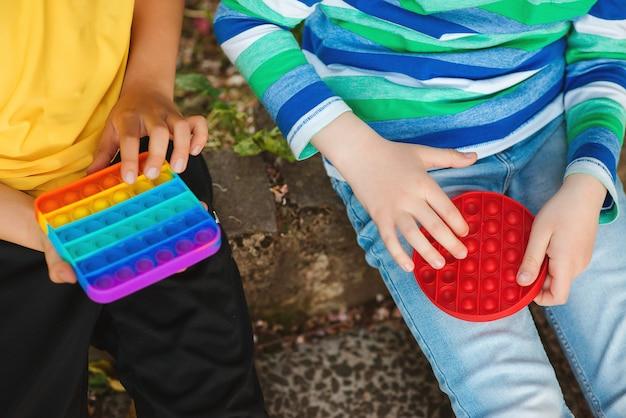 Śliczni chłopcy bawią się modną zabawką pop it. przyjaciele na spacerze z silikonowymi zabawkami bąbelkowymi. chłopcy zabawy na świeżym powietrzu. nowoczesna zabawka antystresowa dla dzieci