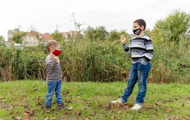 Śliczni chłopcy noszący maskę ochronną w parku jesienią. maska dla dzieci