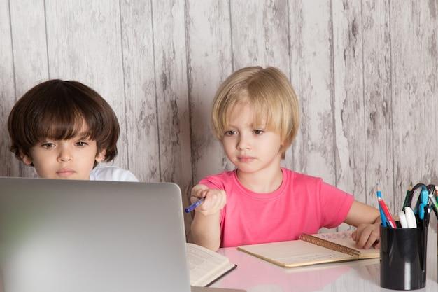 Śliczni chłopcy w różowo-białych koszulkach z szarym laptopem na stole