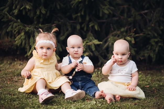 Śliczni dzieciaki siedzi na trawie w parku