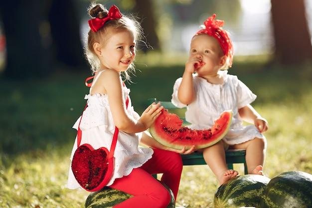 Śliczni małe dzieci z arbuzami w parku