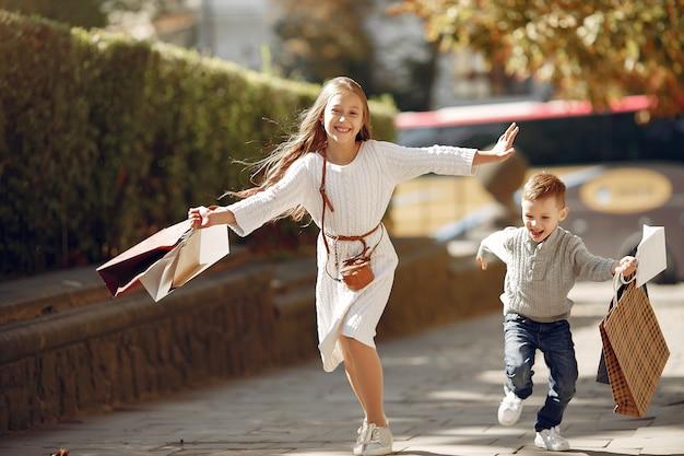 Śliczni małe dzieci z torba na zakupy w mieście