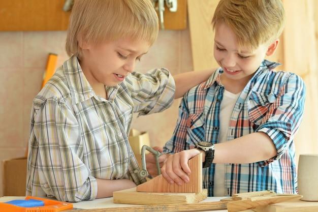 Śliczni mali chłopcy pracujący z drewnem w warsztacie