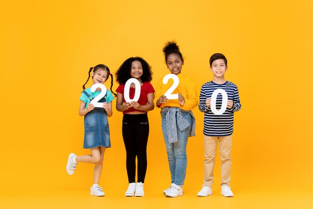 Śliczni mieszani biegowi dzieciaki uśmiecha się 2020 liczby i trzyma
