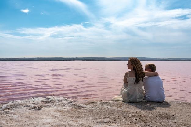 Śliczni nastolatków bracia siedzi na brzeg zadziwiający różowy jezioro
