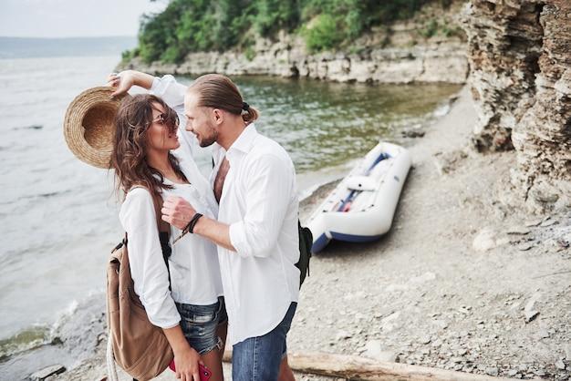 Śliczni potomstwa i para na rzecznym tle. facet i dziewczyna z plecakami podróżują łodzią. koncepcja lato podróżnik