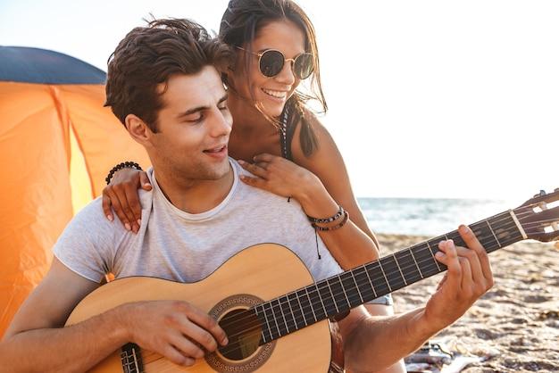 Śliczni przyjaciele kochający para na świeżym powietrzu na plaży, siedząc podczas gry na gitarze