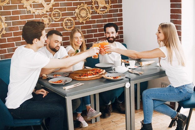 Śliczni przyjaciele w kawiarni je pizza