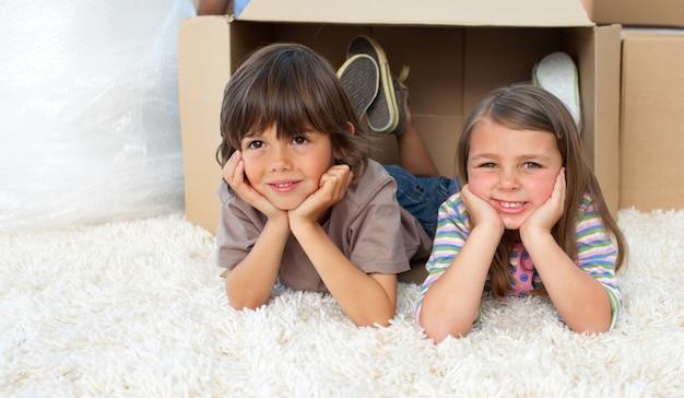 Śliczni rodzeństwa bawić się z pudełkami