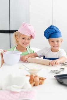 Śliczni rodzeństwa wypiekowi ciastka w kicthen wpólnie