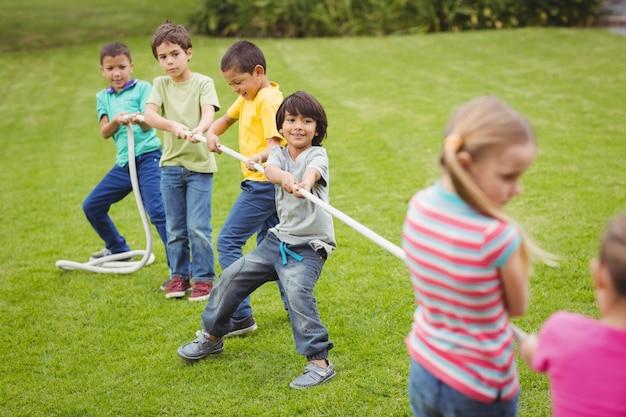 Śliczni ucznie bawić się zażartą rywalizację na trawie outside
