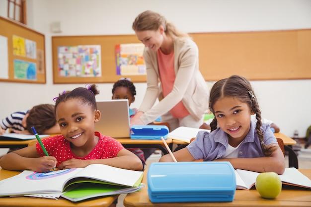 Śliczni ucznie rysuje przy biurkiem w sala lekcyjnej