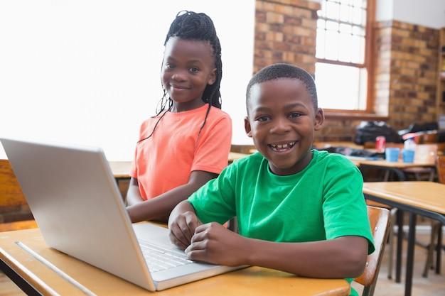 Śliczni ucznie używa laptop w sala lekcyjnej