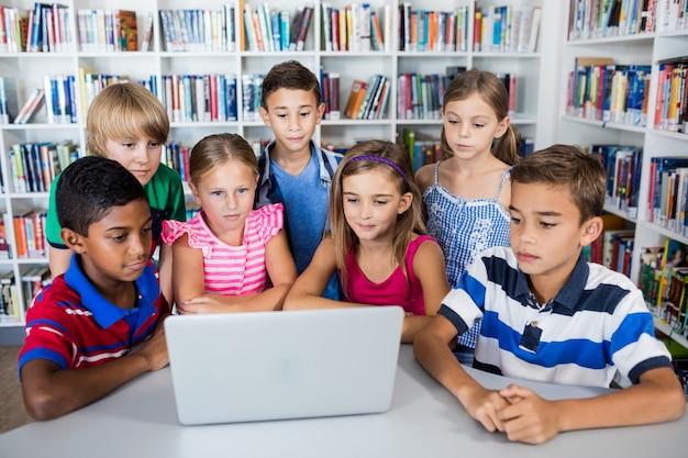 Śliczni uczniowie używa laptop