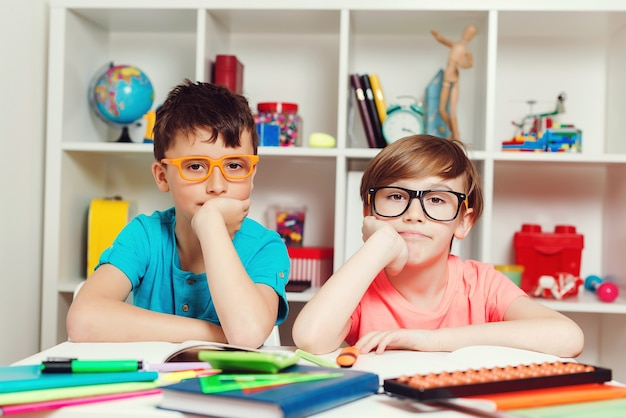 Śliczni uczniowie w klasie w szkole podstawowej. powrót do koncepcji szkoły. portret dwóch mądrych chłopców w pracy w klasie. koncepcja edukacji, uczenia się i ludzi.