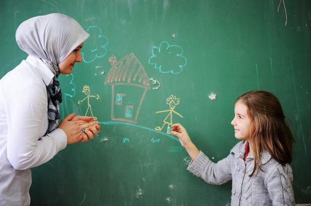 Śliczni uroczy dzieci w wieku szkolnym przy sala lekcyjną ma aktywność edukacyjną