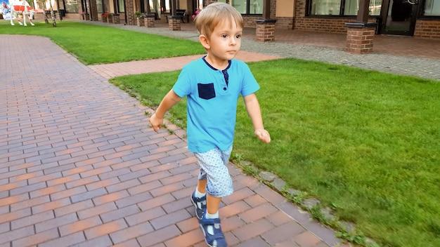 Śliczny 3-letni chłopiec biegający na małej europejskiej ulicy miasta