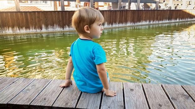 Śliczny 3-letni chłopiec malucha siedzący nad brzegiem rzeki w małym europejskim miasteczku w słoneczny letni dzień