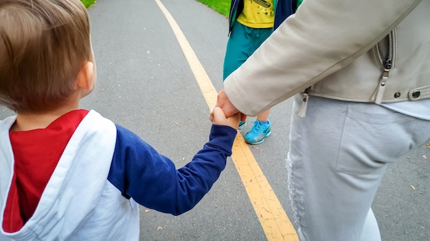 Śliczny 3-letni chłopiec trzymający matkę za rękę i idący ulicą